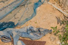 Pair of faded bluejeans laying in dirt. On ground near blue nylon mesh royalty free stock images