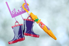 Pair of fashion rubber child boots  hanging with yellow umbrella Royalty Free Stock Images