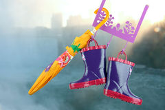 Pair of fashion rubber child boots  hanging with yellow umbrella Royalty Free Stock Photography