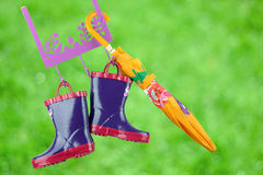 Pair of fashion rubber child boots  hanging with yellow umbrella Stock Images