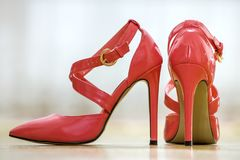 Pair of fashionable high heel leather red cut-out female shoes with golden buckles isolated on light copy space background. Style. And fashion, modern footwear stock image