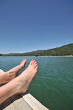A pair of feet on dock by lake Stock Photo
