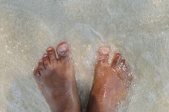 A pair of feet that enjoy a tour on the beach stock photo
