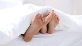Pair of feet playing footsie under the covers stock footage