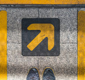 Pair of feet and sign arrow symbol Royalty Free Stock Photography