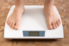 Pair feet standing on the scale. Pair of female feet standing on the scale, closeup stock photo