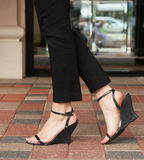 A pair of feet in stylish strappy sandals. Stock Images