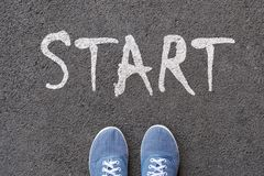 Pair of feet on tarmac road with print of word start for concept of starting point.  stock photo