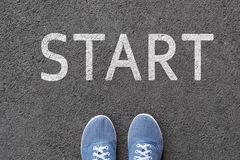 Pair of feet on tarmac road with print of word start for concept of starting point.  royalty free stock images