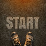 A pair of feet on a tarmac road with white print of the word sta. Rt for the concept of starting point. Start concept background Stock Photography
