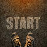 A pair of feet on a tarmac road with white print of the word sta. Rt for the concept of starting point. Start concept background royalty free stock photography