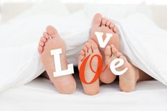 Pair of feet under duvet with love text Stock Photos