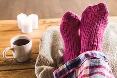 Feet up in cozy woolly pink socks with cup of tea and candles. Pair of feet in warm, woolly socks relaxing on a cushion with mug of tea and candles nearby stock images