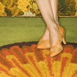 Pair of female feet. Close-up of female feet wearing orange shoes against colorful retro rug stock images