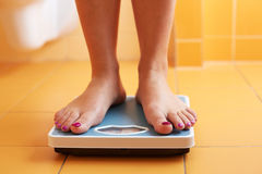 A pair of female feet on a bathroom scale Stock Image