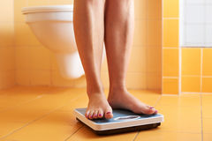 A pair of female feet on a bathroom scale royalty free stock photo