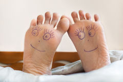Pair of female feet with smiling faces on it. Healthy female feet with smiling faces on it. Joy, health Stock Image