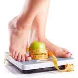 A pair of female feet standing on a bathroom scale with green ap. Ple and tape measure between them stock image