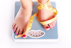 A pair of female feet standing on a bathroom scale. And tape measure between them royalty free stock photography