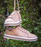 Pair of female leather pink shoes hanging on a string. Close up royalty free stock images