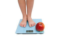 A pair of female legs standing on a bathroom scale Stock Photos