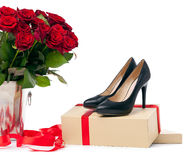 Pair of female shoes and bunch of roses over white Royalty Free Stock Photo