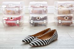 Pair of female shoes and other footwear in plastic boxes on floor. Storage organization stock images