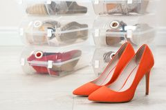 Pair of female shoes and other footwear in plastic boxes on floor. Storage organization royalty free stock image