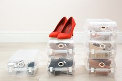 Pair of female shoes and other footwear in plastic boxes on floor. Storage organization royalty free stock photos