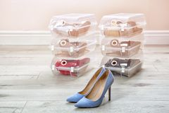 Pair of female shoes and other footwear in plastic boxes on floor. Storage organization stock image