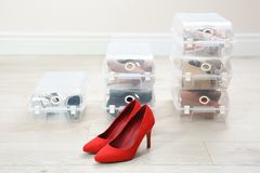 Pair of female shoes and other footwear in plastic boxes on floor. Storage organization stock photography