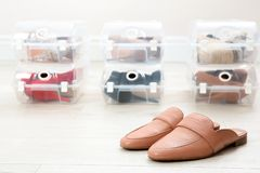 Pair of female shoes and other footwear in plastic boxes on floor. Storage organization royalty free stock photography