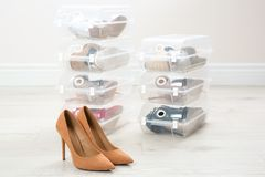 Pair of female shoes and other footwear in plastic boxes on floor. Storage organization royalty free stock photo