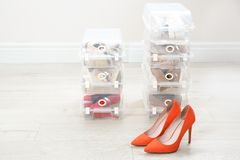Pair of female shoes and other footwear in plastic boxes. On floor. Storage organization royalty free stock image