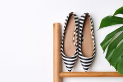 Pair of female shoes on wooden rail. Against white background stock images
