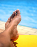 Pair of feminine feet resting on a sun lounger by the pool. In glorious sunshine Royalty Free Stock Image