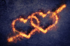 Pair of flaming Valentines hearts. Pair of flaming overlapping Valentines hearts pierced by Cupids arrow of Love over a dark textured background with copyspace Stock Photography