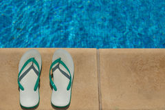Pair of flip flop thongs on the side of a swimming Stock Images