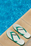 Pair of flip flop thongs on the side of a swimming Royalty Free Stock Images