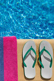Pair of flip flop thongs and the side of a towel o Stock Image