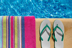 Pair of flip flop thongs and the side of a towel t Royalty Free Stock Images
