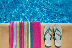 Pair of flip flop thongs and a towel on the side o Royalty Free Stock Images