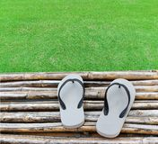 A pair of flip flops on bamboo and green grass Royalty Free Stock Photography