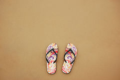 A pair of flip flops on the beach sand, Summer back concept.  Stock Photo