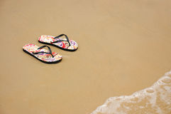 A pair of flip flops on the beach sand, Summer back concept. Royalty Free Stock Photos