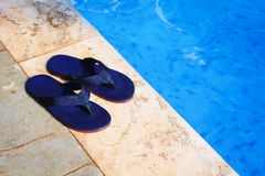 Pair flip flops at the edge of a swimming pool Royalty Free Stock Images