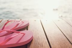 A pair of flip flops on the pier. At the sunset. Horizontal royalty free stock images