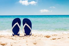 Pair of flip flops on tropical sand beach in summer. Pair of flip flops on sand beach with tropical blue sea and sky in background in summer stock images