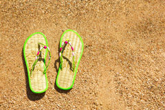 Pair of flip-flops in the wet sand Royalty Free Stock Photo