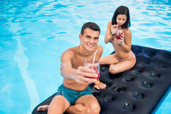 Pair floating on an inflatable mattress in swimming pool, drinking cocktails and having fun on their summer vacation Royalty Free Stock Photography
